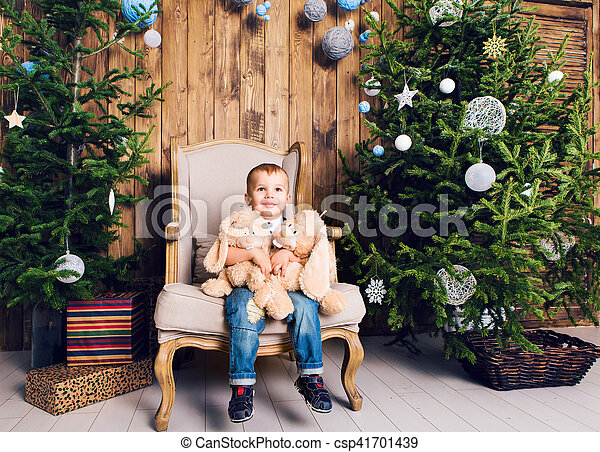 Happy little boy playing near the Christmas tree - csp41701439