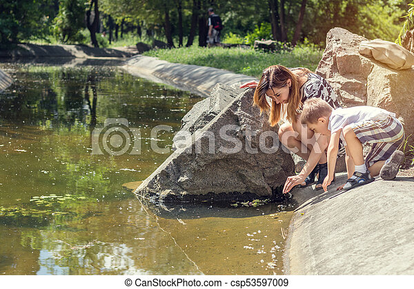 Happy little boy playing with his mother in the city park on a summer sunny day. Mother and son in the park near pond. - csp53597009