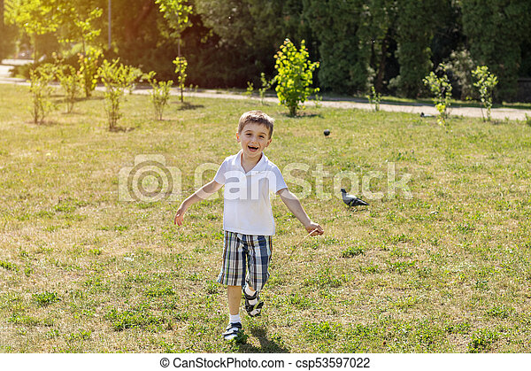 Happy little boy running on a lawn in the city park on a summer sunny day. Close up. Beautiful summer background with copy space - csp53597022