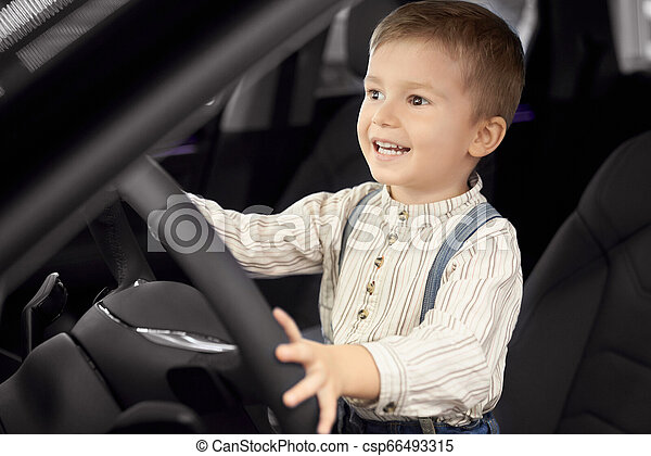 Happy little boy sitting in driver's seat, smiling. - csp66493315