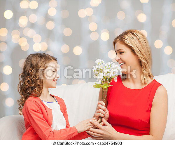 happy little daughter giving flowers to her mother - csp24754903