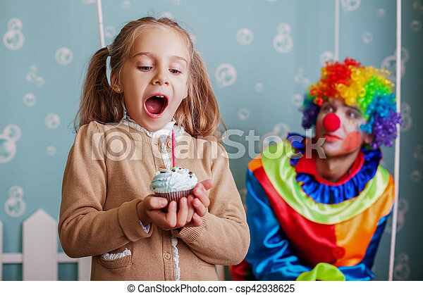 Happy little girl blows out the candle on cake. - csp42938625