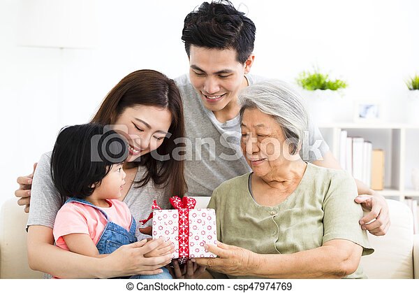 happy little girl giving present to her grandmother