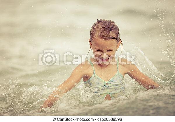 happy little girl splashing in the sea - csp20589596