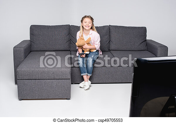 Terrific Happy Little Girl With Teddy Bear Sitting On Sofa And Watching Tv Bralicious Painted Fabric Chair Ideas Braliciousco