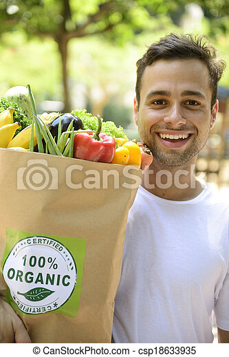 Happy man carrying bag of organic food. - csp18633935