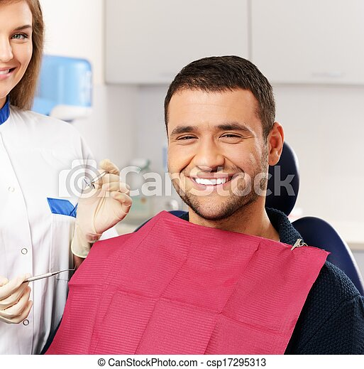 Happy man patient and smiling woman dentist at dental surgery - csp17295313