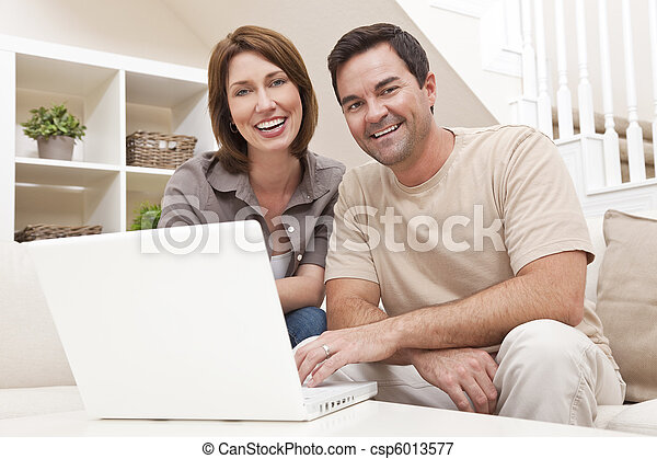 Happy Man Woman Couple Using Laptop Computer At Home - csp6013577