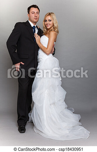 Happy married couple bride groom on gray background - csp18430951