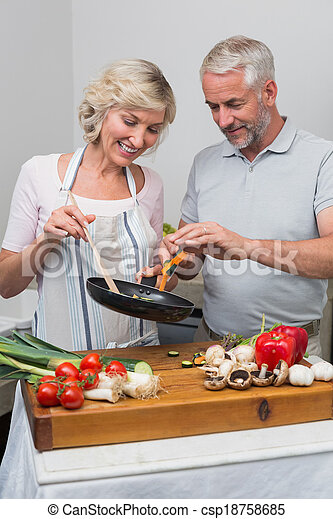 Happy mature couple preparing food together in kitchen - csp18758685
