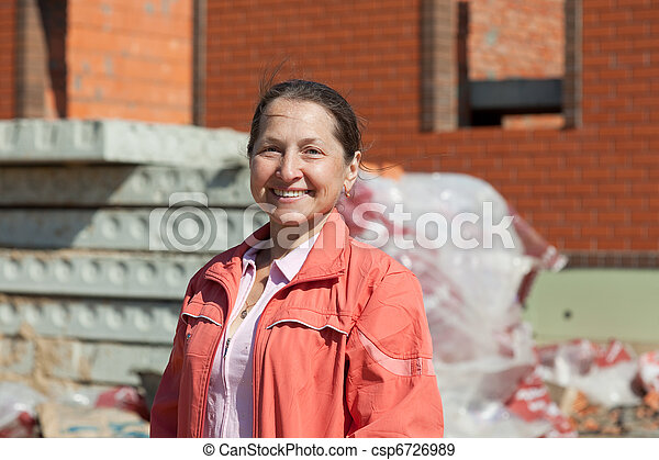 Happy mature woman against building residence - csp6726989