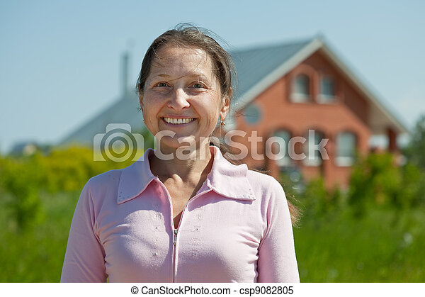 Happy  mature woman  against  home - csp9082805