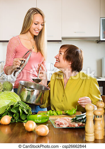 Happy mature woman with adult daughter cooking  together - csp26662844