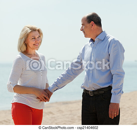 happy mature woman with  man against sea - csp21404602