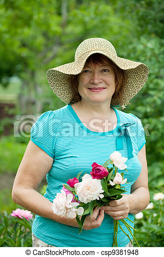 Happy mature woman with peony  - csp9381948