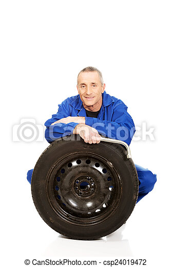 Happy mechanic with a tire and wrench - csp24019472