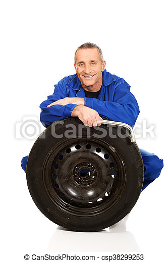 Happy mechanic with a tire and wrench - csp38299253