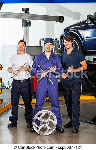 Happy Mechanics Holding Wrenches At Garage - csp36877121