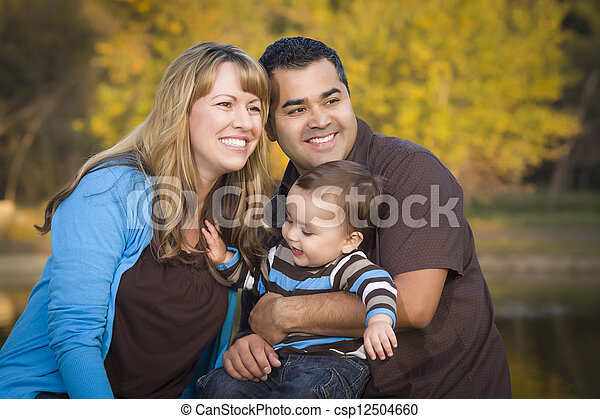 Happy Mixed Race Ethnic Family Playing In The Park - csp12504660
