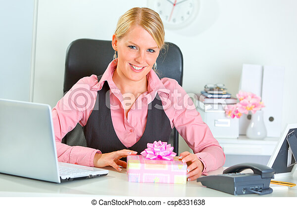 Happy modern business woman with present box at office desk - csp8331638