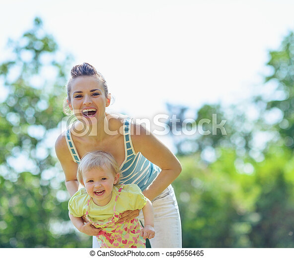 Happy mother and baby playing outside - csp9556465