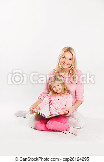 happy mother and child reading a book together - csp26124295