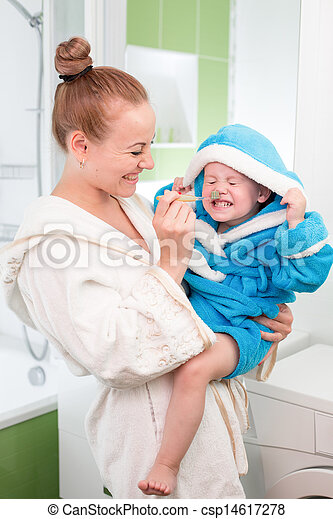 Happy mother and child teeth brushing together in bathroom - csp14617278