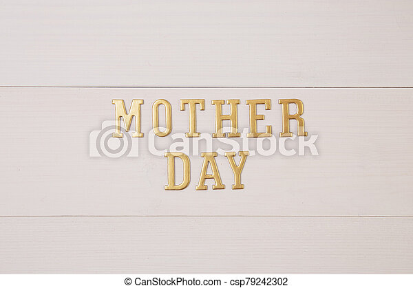 Happy mother day with gold text on wooden table, feeling romantic and care with decoration, word and alphabet mother day in festive with sign on desk, congratulation, top view, holiday concept. - csp79242302