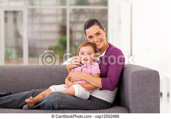 happy mother hugging daughter on sofa - csp12552486
