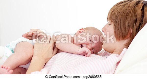 Happy mother kissing her newborn baby - csp2080565