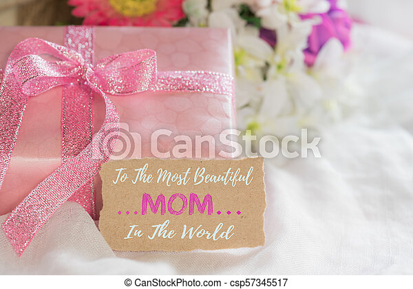 Happy mother's day concept. Pink Gift box with purple flower, paper tag  on white cheesecloth background. - csp57345517