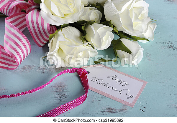 Happy Mothers Day gift of white roses bouquet with pink stripe ribbon and gift tag with greeting on aqua blue vintage shabby chic table. - csp31995892