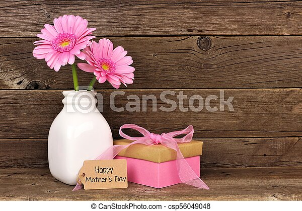 Happy Mothers Day tag with gift and pink flowers against rustic wood - csp56049048