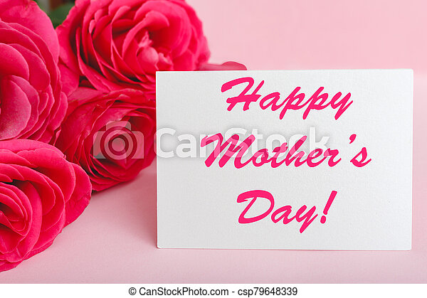 Happy Mothers Day text on gift card in flower bouquet of pink roses on pink background. Greeting card for Mom. Flower delivery, Congratulations card in flowers for women. Greeting card in roses - csp79648339