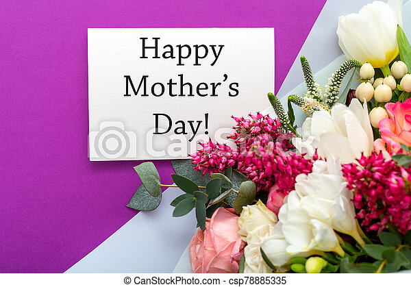 Happy Mothers Day text on gift card with flower bouquet of roses, tulips, eucalyptus on purple background. Greeting card for Mom. Flower delivery, Congratulations Greeting card and flowers for mother. - csp78885335