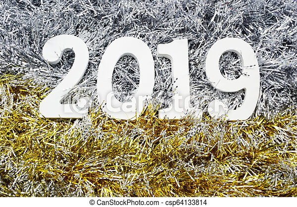 Happy New Year 2019 wooden number on shiny tinsel background - csp64133814