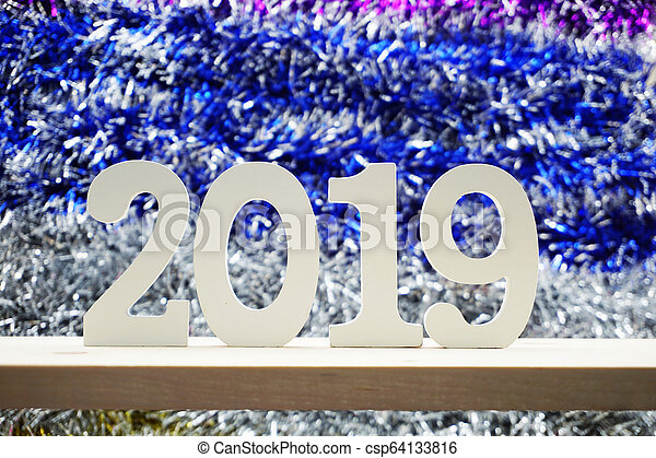 Happy New Year 2019 wooden number on shiny tinsel background - csp64133816