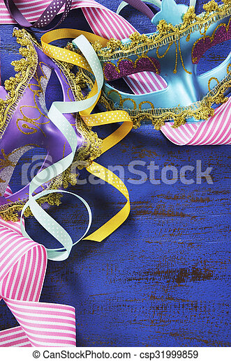 happy new year background with pink purple and blue masquerade party masks and decorations on dark blue rustic distressed vintage wood vertical closeup