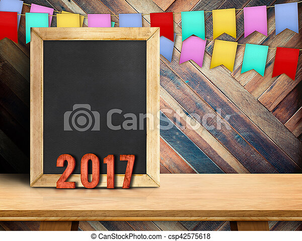Happy new year on blackboard with gift and colorful flag banner on wood table at diagonal wood wall, Leave space for display or montage of your design - csp42575618