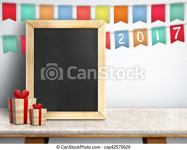 Happy new year on blackboard with gift and colorful flag banner on marble table at white wall, Leave space for display or montage of your design - csp42575629