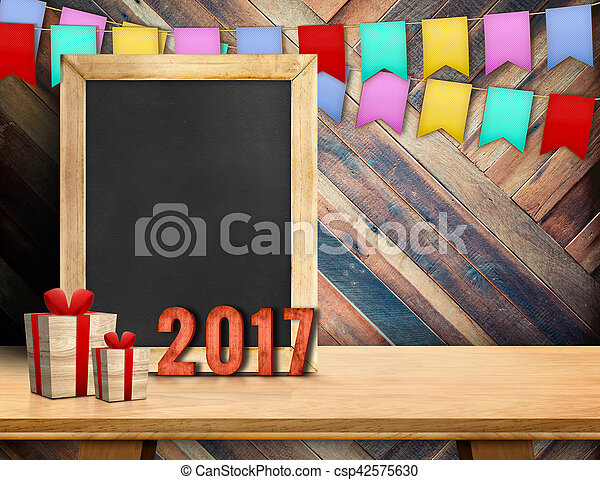 Happy new year on blackboard with gift and colorful flag banner on wood table at diagonal wood wall, Leave space for display or montage of your design - csp42575630