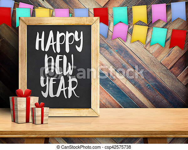 Happy new year on blackboard with gift and colorful flag banner on wood table at diagonal wood wall, Leave space for display or montage of your design - csp42575738