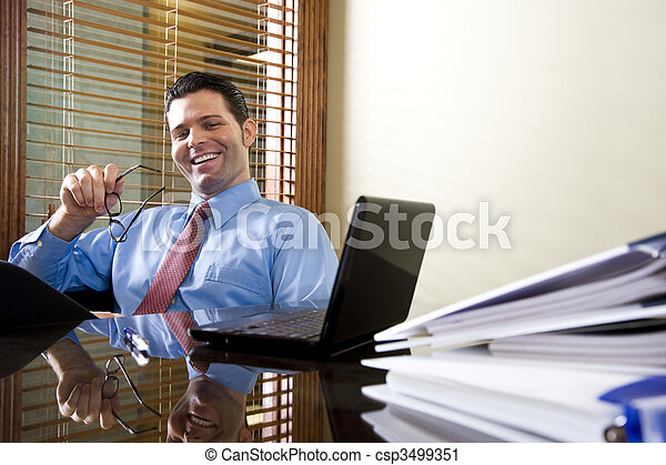 Happy office worker working on laptop computer - csp3499351