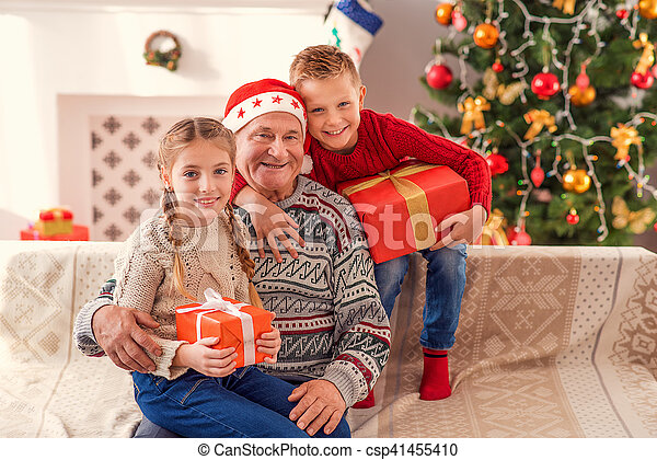 Happy old man with his grandchildren on christmas. Friendly family ...