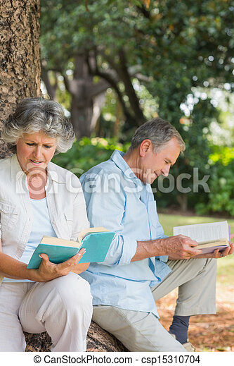 Happy older couple reading books together sitting on tree trunk - csp15310704