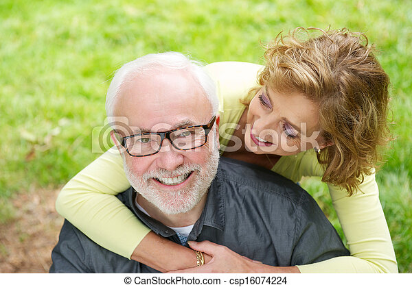 Happy older man with beautiful woman smiling outdoors - csp16074224