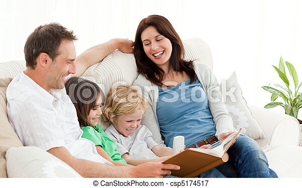 Happy parents looking at a photo album with their children - csp5174517