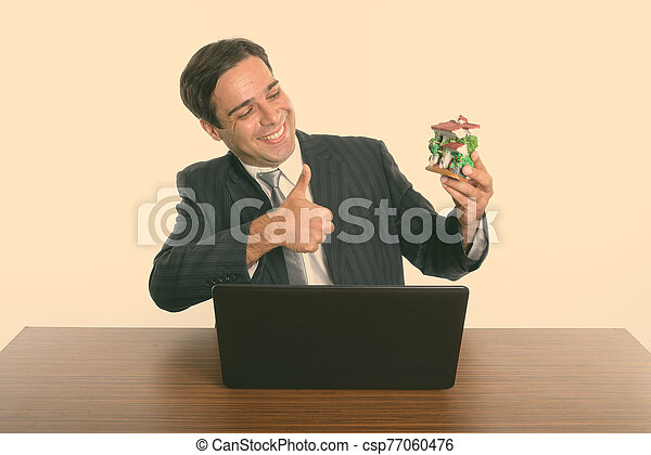 Happy Persian businessman looking at house figurine and giving thumbs up on wooden table - csp77060476