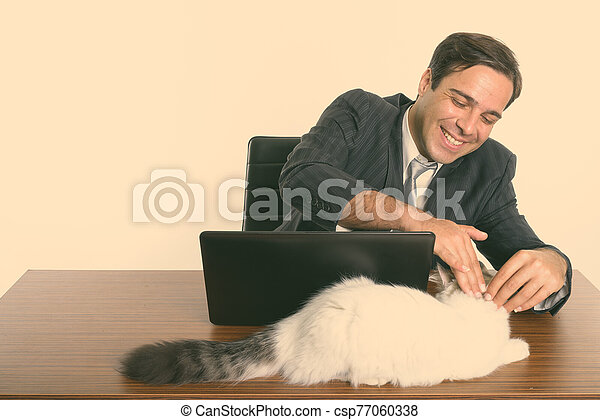 Happy Persian businessman smiling and touching cute cat while sitting with laptop on wooden table - csp77060338