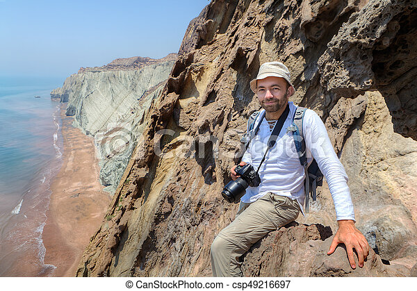 Happy photographer traveler sitting on the edge of a cliff. - csp49216697